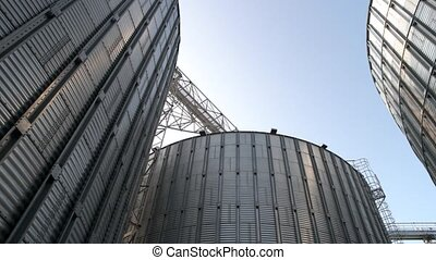 Stainless steel grain bins, up view. Gather of metal...