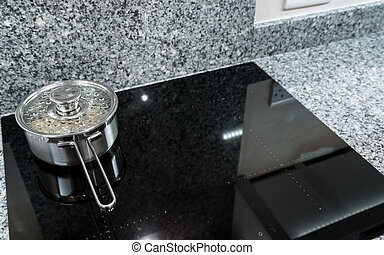 Stainless steel pan on modern induction hob or cooktop -...