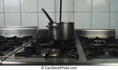 stainless steel stock pot is on a greasy dirty gas stove in...
