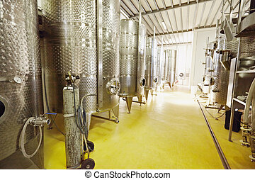 Stainless steel wine fermentation containers in a winery -...