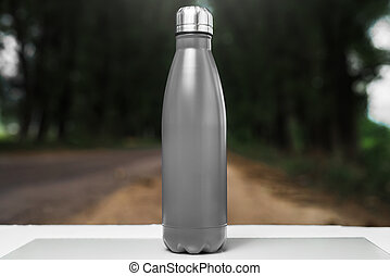 Stainless thermos water bottle on white table, outdoor. Black color.