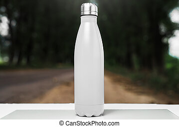 Stainless thermos water bottle on white table, outdoor. White color.