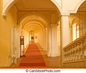 Staircase and yellow gallery of arches with chandelier...