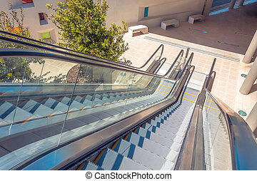 Staircase escalator bottom view on the outside street in the courtyard of the building. Look down descent view.