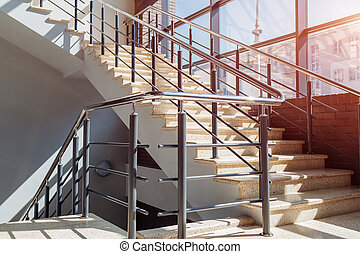 Staircase in modern buisness center building. Emergency exit. Stairs in shopping center. White ladder by window