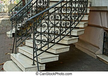 Staircase with gray concrete steps and iron black handrails with a forged pattern near the wall on the sidewalk