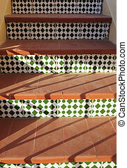 Staircase with green Spanish mosaic pattern and terracotta steps