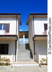 Stairs between the two white concrete two-story houses with balconies