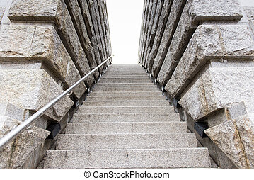 Stone stairs leading upwards into a white sky outdoors