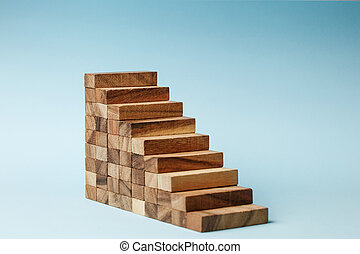 Stairs of wooden blocks on blue background.