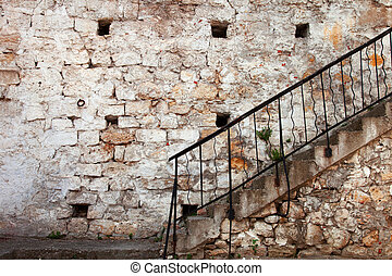 Stairs with railing against the old stone walls