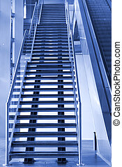Stairway and Escalator going up in an Airport.