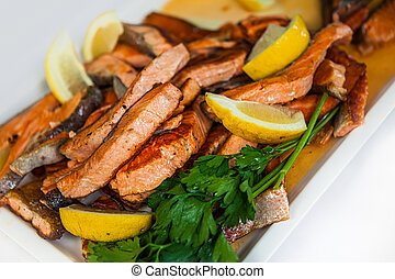 Stakes from a salmon with lemon on a plate