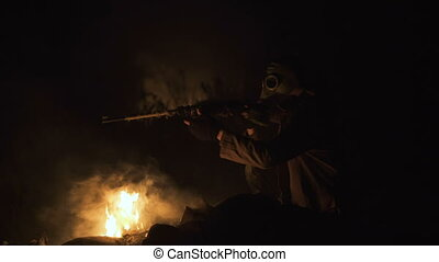 Stalker survivor Soldier wearing Gas Mask in an Apocalypse War scenario Sitting with old-style rifle and taking aim near the fire