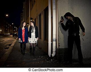 Hooded man stalking two women behind a corner holding a gun