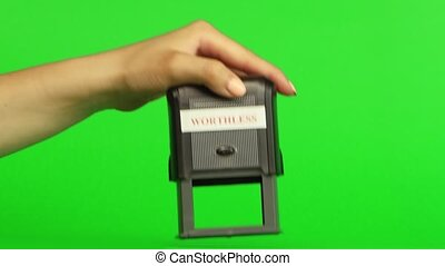 Stamp WORTHLESS. Close up. Green screen