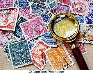 A collection of used Austrian stamps with a small elegant magnifying glass