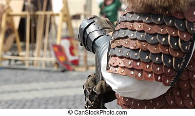 Stand up knight with protective leather gloves and armor.