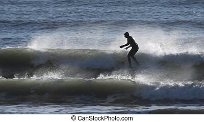 A surfer with paddle and wetsuit riding a wave in Kachemak Bay amidst wind-driven spray.