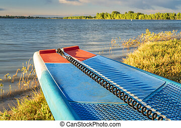 stand up paddleboard with a safety leash on a lake shore in Colorado (Boyd Lake State Park), summer scenery
