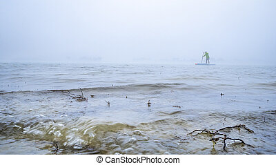 stand up paddler on a foggy lake