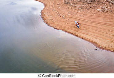 stand up paddler on a lake shore