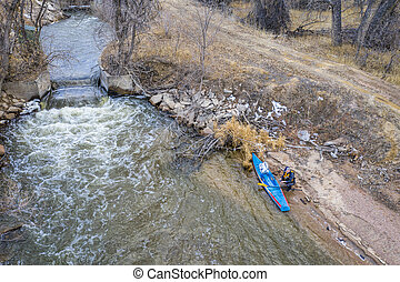 Stand up paddler on a river shore