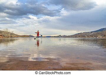 stand up paddling in winter season - senior male paddler in ...