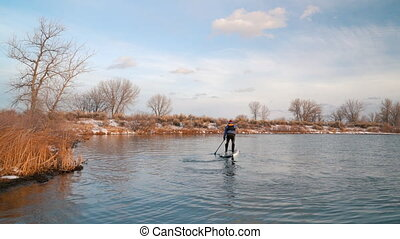 Stand up paddling on a lake in Colorado, winter or early spring scenery with some snow