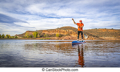 stand up paddling on mountain lake - A senior male paddling ...