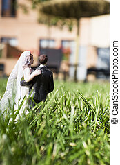 Standard figure of wedding couple on natural grass in the field