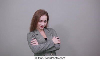 Standing and cross arms on chest. Young attractive woman, dressed gray jacket