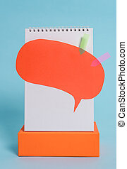 Standing blank spiral notepad speech bubble arrow banners rectangular box above lying cool pastel retro background. Empty text important future events.