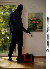 Standing burglar in house - A standing burglar with a bag in...