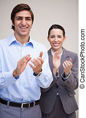 Standing business team clapping
