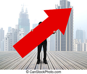 standing businessman holding red arrow sign