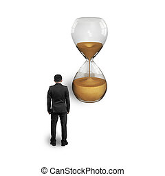 standing businessman thinking and looking at hourglass
