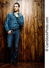 standing by the wall - Jeans style. Full length portrait of...