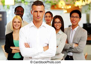 standing, colleghi, suo, bracci piegati, fronte, uomo affari, bello
