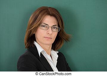 standing, contro, chalkboard verde, insegnante femmina