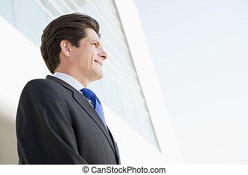 standing, costruzione, sorridente, uomo affari, fuori