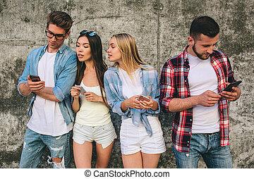 standing, dall'aspetto, destra, phones., essi, persone, grigio, concentrated., giovane, insieme, amd, quattro, loro, soltanto, occupato, fondo, serio, sorridente, tipo, bit.