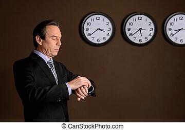 standing, differente, suo, controllo, esposizione, orologio, time., dall'aspetto, fiducioso, mentre, clocks, maturo, tempo, fronte, uomo affari, parete