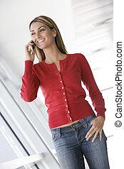 standing, donna, corridoio, telefono, cellulare, usando, sorridente