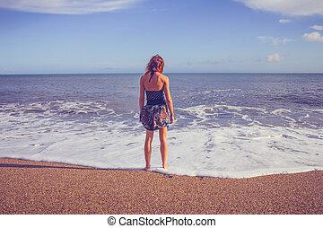 standing, donna, giovane guardare, mare, spiaggia, vista posteriore