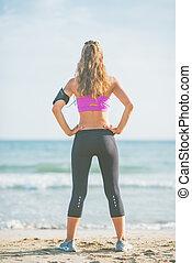 standing, donna, giovane, spiaggia., idoneità, vista posteriore