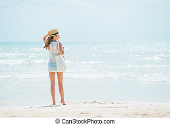 standing, donna, giovane, spiaggia., vista posteriore