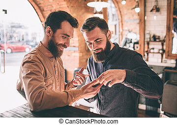 standing, guy., loro, esposizione, due, insieme, uno, dall'aspetto, telefono, altro, telefono., qualcosa, essi, barbershop., amici, felice
