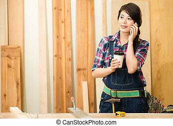 standing in workshop talking on phone