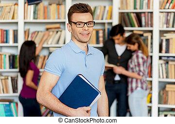 standing, libro, mentre, suo, persone, exam., tre, lui, giovane, altro, scaffale, dietro, macchina fotografica, presa a terra, pronto, uomo sorridente, finale, bello